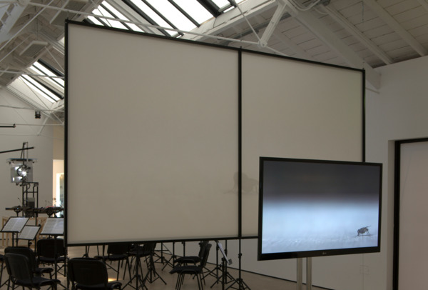 Henrik Håkansson, The End, 2011, Film installation: 35mm projection, 2 monitors, 2 speakers, 5 digital film stills framed, 14 chairs, 21 music stands, Film duration: 12 mins 40 secs looped, Framed digital film stills 51 x 81 x 3.5 cm each, Installation view, 'The End', The Modern Institute, Osborne Street, Glasgow, 2011