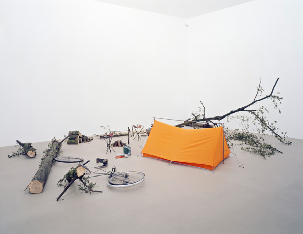 Simon Starling, Carbon (Pederson), 2003, Two bicycles, orange tent, two stools, two chain saws, cooking spit, gloves, petrol can, oil, bike lamps, tree