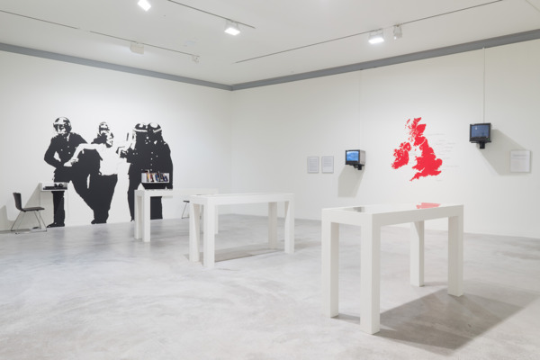The Battle of Orgreave (An Injury to One is an Injury to All), 2004, Archive including: Vinyl lettering and map, archive material, 2 DVD/monitors, CD and player, books, DVD/projection room, wall painting, Installation view 'Joy In People', Contemporary Art Museum, St. Louis, 2013