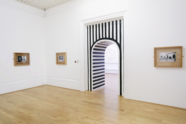 The Reiterative Grimace, 2013, Two portals: MDF, timber, paint; Ten framed B&W photographs: Plywood, glass, brass mirror plates, B&W photographs, Two portals: 500 x 280 x 80 cm; Photographs: 60.5 x 72.5 x 6.5 cm each, Installation view 'Northern Art Prize', Leeds Art Gallery, Leeds, 2013