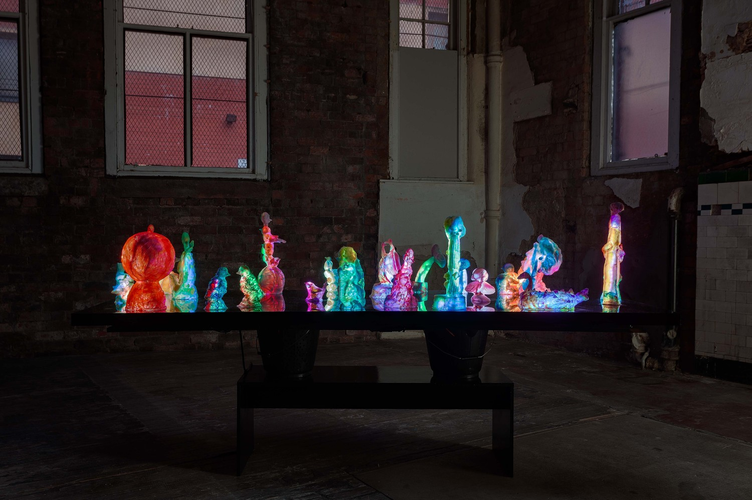 To Disturb Somnolent Birds, 2020, Perspex table, 19 resin and pigment sculpture with LED strip, WiFI controller, electronic, components, Jesmonite buckets with speakers, looped soundtrack, wooden bench, Overall dimensions: 120 x 240 x 93 cm